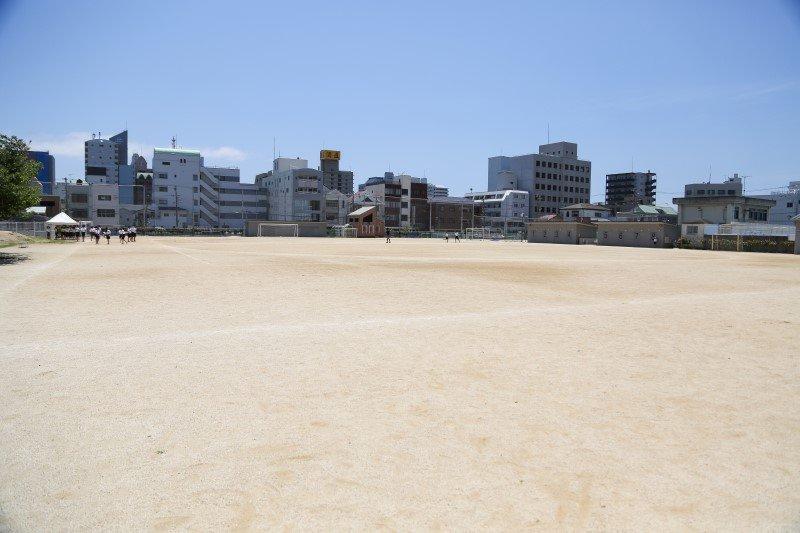広い運動場。奥にはテニスコート、プール、学校菜園がある。